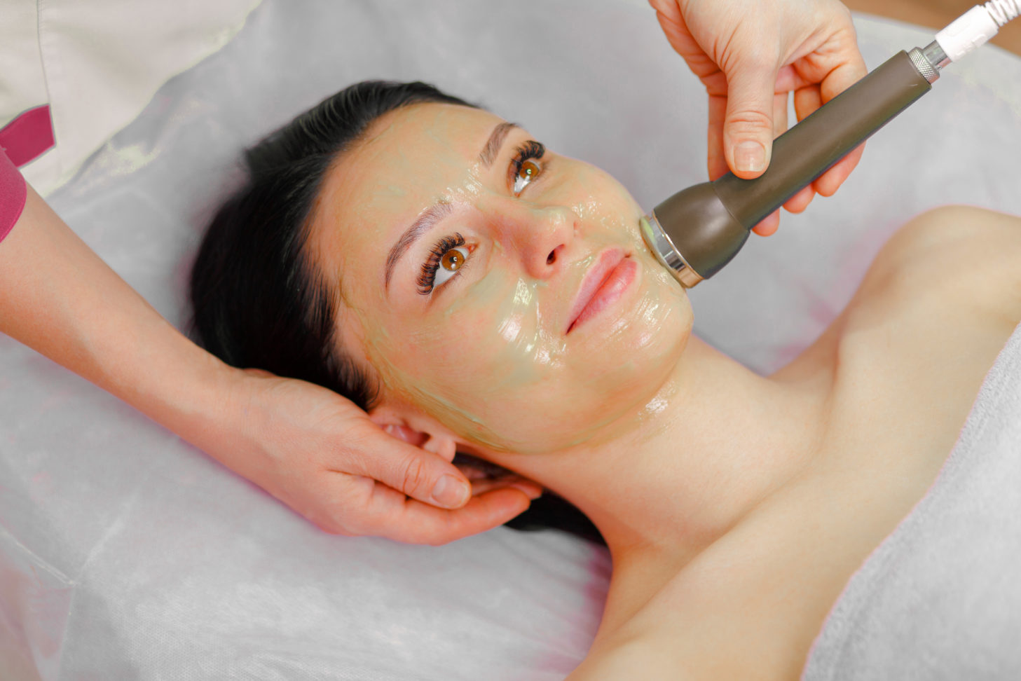 Face Skin Care. Young beautiful woman with dark hair gets procedure in the beauty salon.  Ultrasound Cavitation anti-aging, Rejuvenation, Lifting Procedure. Beauty Concept